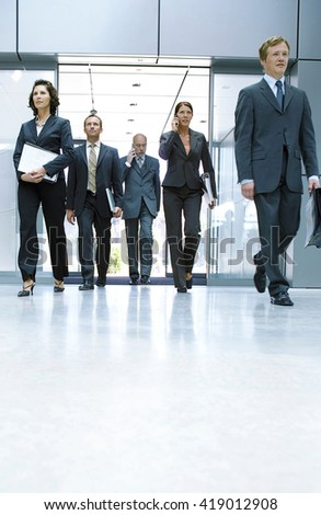 Portrait Of Business Team walking inside the Office - stock photo