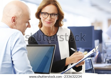 Portrait of business woman holding clipboard while discussing sales man at office.  - stock photo
