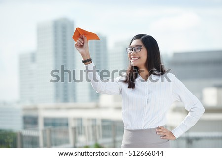 Portrait of business woman launching paper airplane