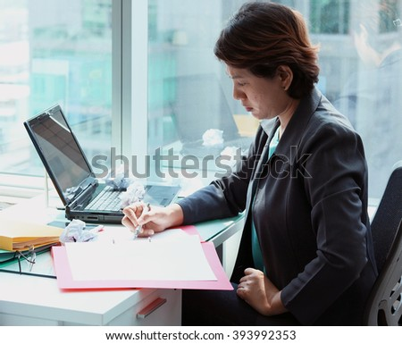 Portrait of business woman looking at document on the desk