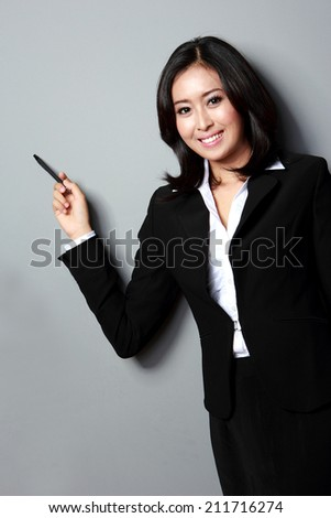 portrait of business woman presenting. on grey background - stock photo