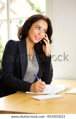 Portrait of business woman sitting in office talking on phone