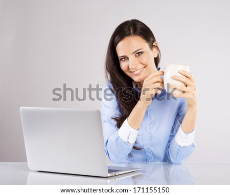 Portrait of Business woman sitting on her desk working with laptop isolated over gray background.