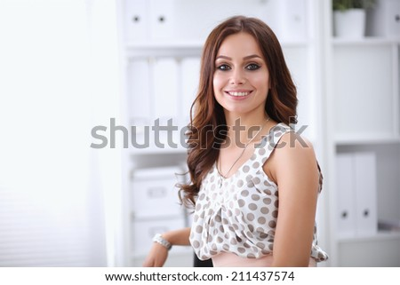 Portrait of business woman standing in office - stock photo