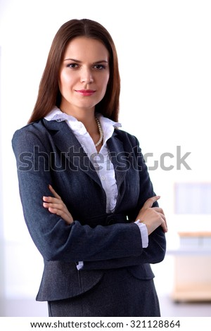 Portrait of business woman standing with crossed arms in office - stock photo