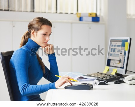 portrait of business woman typing on calculator - stock photo