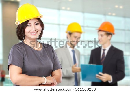 portrait of business woman wear a safety helmet. with team discussing at the background