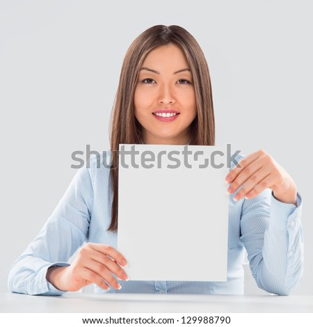 Portrait of business woman with blank sheet over gray background - stock photo