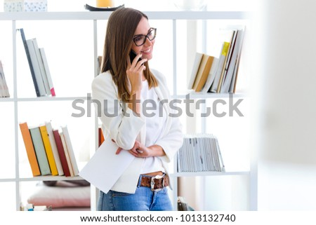 Portrait of business young woman using her mobile phone in the office.
