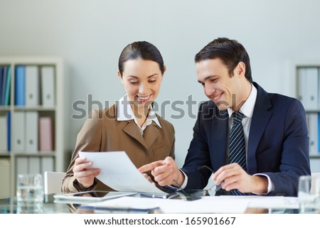 Portrait of businessman and businesswoman discussing paper at meeting