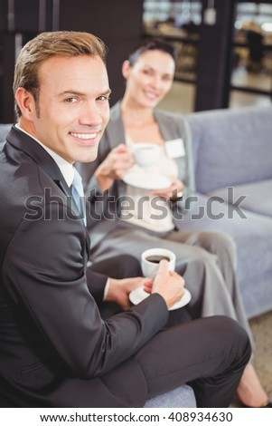 Portrait of businessman and businesswoman having tea during breaktime in office - stock photo