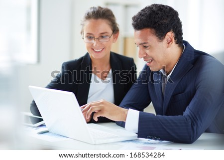 Portrait of businessman and businesswoman looking at laptop display at meeting - stock photo
