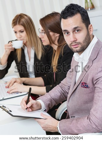 Portrait of businessman at busy office, two beautiful business woman in background.