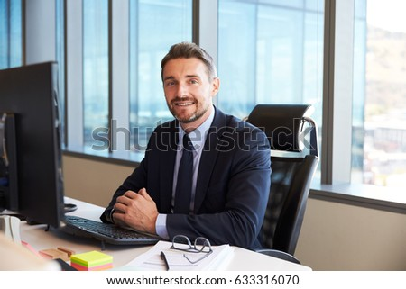 Portrait Of Businessman At Office Desk Using Computer