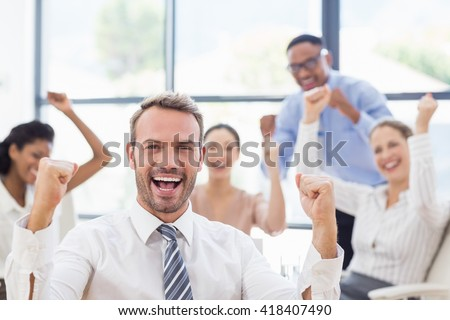 Portrait of businessman celebrating success in office with her colleagues - stock photo