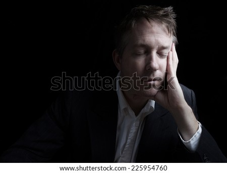 Portrait of businessman closing eyes while working late at night on black background with copy space  - stock photo