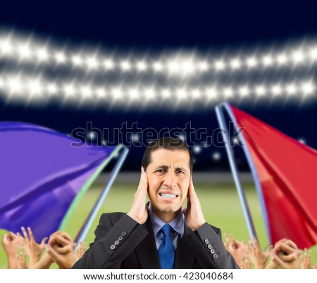 Portrait of businessman covering his ears with hand to not hear the chants in the stadium - stock photo