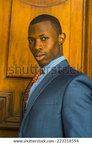 Portrait of Businessman. Dressing formally in blue suit, patterned shirt and necktie, wearing ear stud, short haircut, a young guy is standing in the front of an old style office door, looking at you. - stock photo