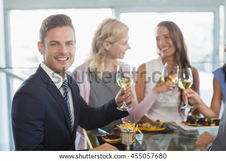 Portrait of businessman having lunch with his colleagues at a restaurant - stock photo