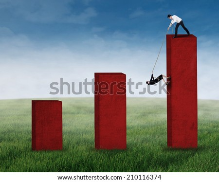 Portrait of businessman help his partner to climb the business chart by pulling her with a rope - stock photo