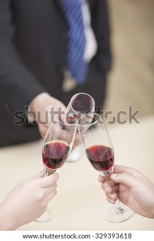 Portrait of businessman holding a glass of wine and toasting,close-up - stock photo