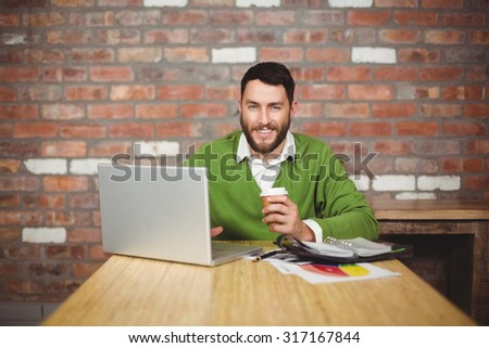Portrait of businessman holding coffee while working on laptop in creative office - stock photo
