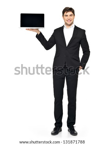 Portrait of  businessman holds on palm the opened  laptop with blank black screen isolated on white. - stock photo