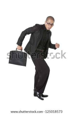 Portrait of businessman hurrying somewhere with a suitcase