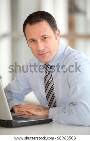 Portrait of businessman in front of laptop computer - stock photo
