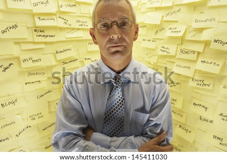 Portrait of businessman in front of wall covered in sticky notes - stock photo