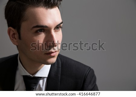 Portrait of businessman in suit on grey background