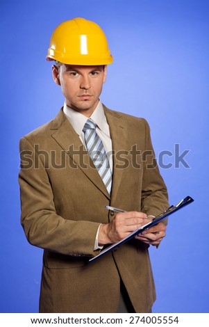 Portrait of businessman in yellow hardhat writing on clipboard - stock photo