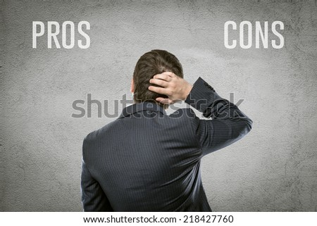 """Portrait of businessman making risk research standing at wall with """"pros ans cons"""" title. Young stock broker analyzing financial and investment strategy.  - stock photo"""