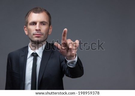 Portrait of businessman pointing finger gestures, isolated on grey background. Concept of leadership and success - stock photo