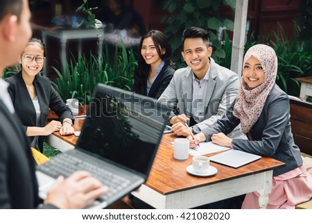 portrait of businessman presentation at a cafe with team - stock photo