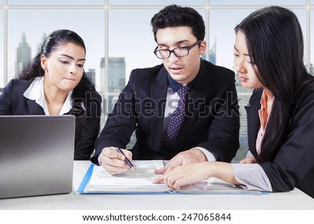 Portrait of businessman reading and signing a business document with his partners - stock photo