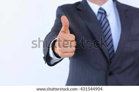 Portrait of businessman showing thumbs up hand sign.