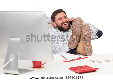 Portrait of businessman sitting and puting your feet up on the table and talking on mobile phone in office - stock photo