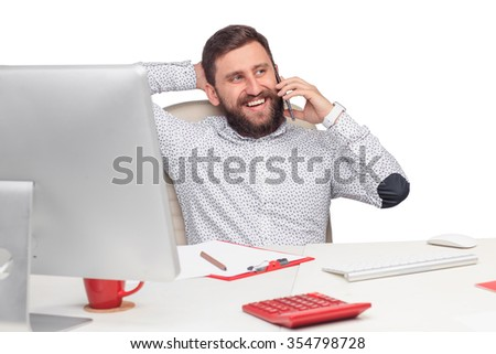 Portrait of businessman sitting and talking on mobile phone in office