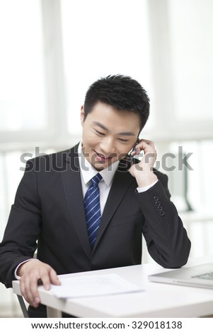 Portrait of businessman sitting at desk and using cell phone