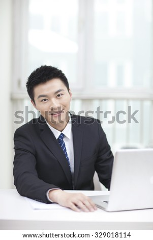 Portrait of businessman sitting by laptop