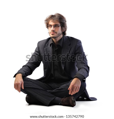 portrait of businessman sitting with cross-legged on the floor - stock photo