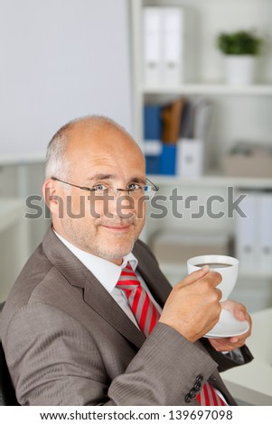 portrait of businessman smiling and having a cup of coffee - stock photo