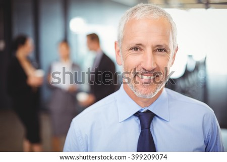 Portrait of businessman smiling in office - stock photo