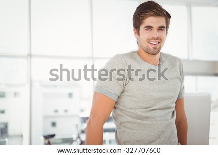 Portrait of businessman smiling while standing against window in office - stock photo