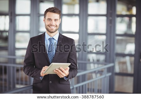Portrait of businessman smiling while using digital tablet in office - stock photo