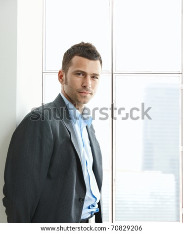 Portrait of businessman standing at office window, looking at camera, smiling.? - stock photo