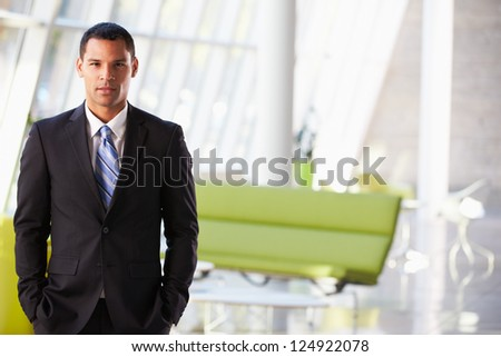 Portrait Of Businessman Standing Modern Office Reception - stock photo
