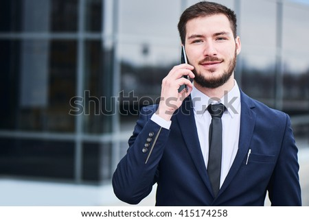 Portrait of businessman talking on cell phone against the building with a glass facade