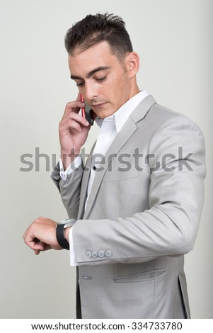 Portrait of businessman talking on phone and looking his watch - stock photo